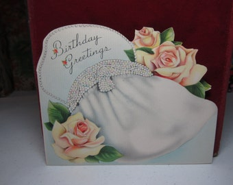 1940's evening bag graphics birthday card with small die cut graphics of a compact, lipstick, key chain,etc. open to reveal birthday wishes