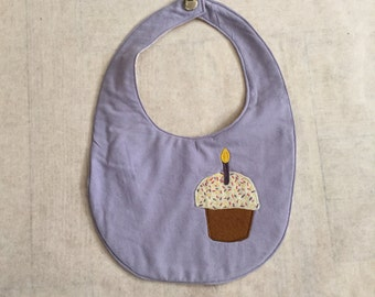 Cupcake Birthday bib in lavender with tree trunk cross sections on reverse