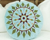Round pillow in turquoise velvet with an embroidery inspired by a Dreamcatcher