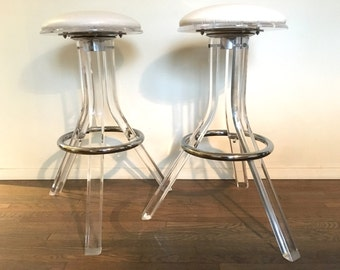 pair of midcentury modern lucite and chrome with white vinyl bar stools
