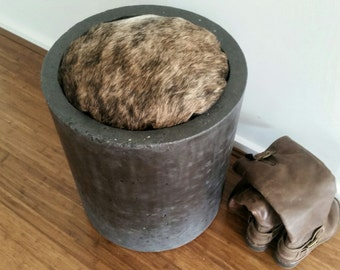 Concrete stool, polished charcoal concrete indoor ottoman. Cylinder chair or seat with cowhide cusion top.