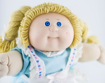 Vintage Coleco Cabbage Patch Doll with blonde yarn hair and blue eyes in a dutch outfit with tights and shoes