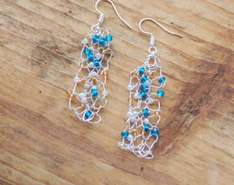 Knitted jewellery; beaded earrings in blue, gold and white