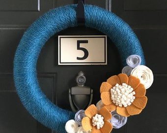 Teal yarn wreath with mustard flowers