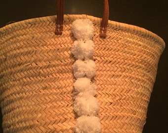 French market basket with white pom poms and leather handles