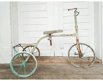 Vintage tricycle with wooden seat and turquoise wheels. Antique tricycle, outdoor decoration, Vintage bicycles, antique toys