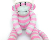 Small pink and grey striped sock monkey with pink and cream spot pom pom hat