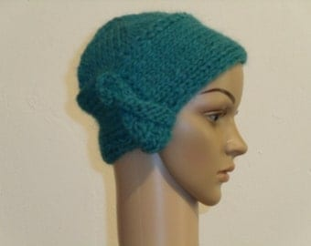 Knitted soft Cap with a decoration on the edge in blue-green
