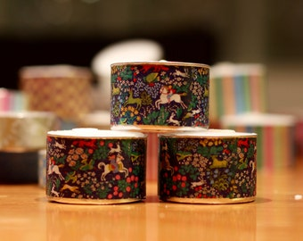 3 extra-tall tea light candles decorated with medieval-style pattern of horses, riders, animals, and flowers