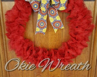 Red frayed ruffle burlap wreath with red, yellow and blue bow