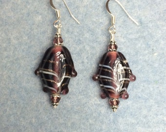 Raspberry purple transparent lampwork fish bead dangle earrings adorned with purple crystal beads.