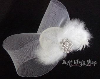 white fascinator, white feathers and rhinestone centre.