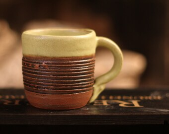 Beautifully textured wheel-thrown mug with olive green glaze and leather look texture