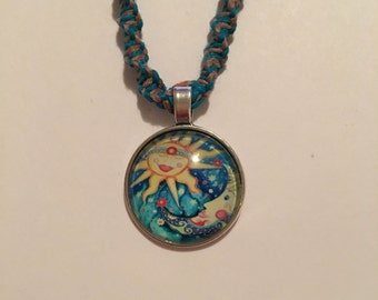 Handmade blue and natural hemp necklace with a glass moon and star round pendant