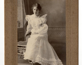 Full length cabinet card photo of pretty young woman in white gloves and with messy hair.