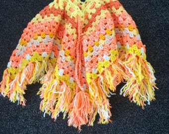 A Childres Crocheted Poncho In Lemon, Orange and White