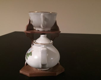 Dainty miniature tea pot and tea cup in bone china on lovely stand.