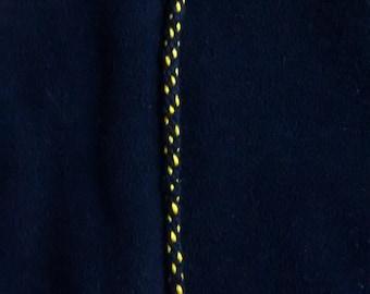Black bracelet with yellow dots.