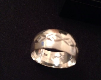 A wide engraved sterling silver band.