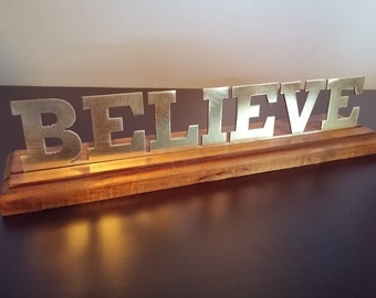 """Steel """"Believe"""" with finished wood base"""