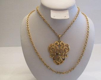 Beautiful marked TRIFARI scroll design pendant on a double strand goldtone chain