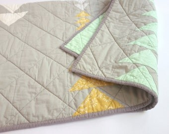 Grey baby quilt with triangles. Flying geese (traditional quilt block) design. Minty green and gold accents.
