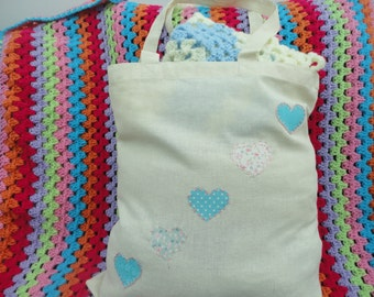 Canvas bag with five handstiched hearts embroidered onto the front