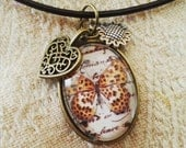 Butterfly cabochon pendant in bronze on a brown cord necklace with flower (silver) and heart (bronze) charms