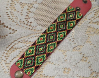 Seed bead bracelet on leather. rasta colors on red leather