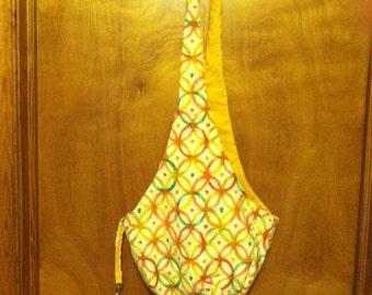 pet sling in orange, green, white and yellow