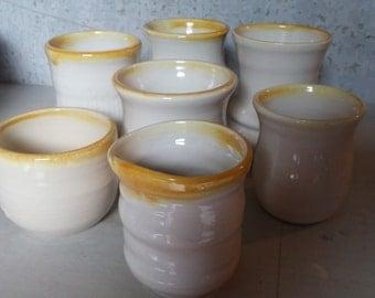 White stoneware hand thrown cups. Mustard trim.