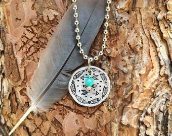 Hand stamped feather and arrow aluminum disk necklace.