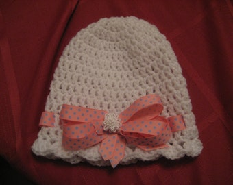 white hand crochet hat with pink ribbon with blue dots