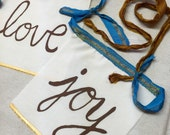 Ready to Ship!  Peace, Love, Joy.  String of 3 Flags.  Dark brown + gold ink.  Recycled sari ribbon in Bronze + Blue with Gold.