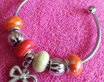 BRACELET: Fashionable Silver Cuff Bracelet with Red, Orange and Green Lampwork Beads and a Darling Bow Charm