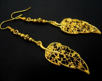 A pair of pretty gold colour long dangly leaf themed earrings.