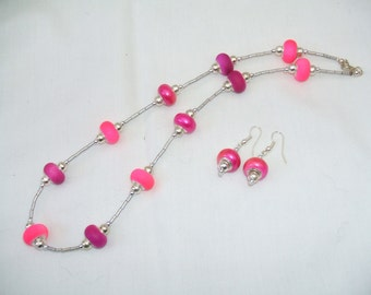 Pink charm style beaded necklace and matching earrings.