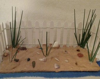 White Picket Fence with Sand and Seashells and Dune Grass