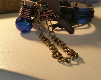 Key + Vial Bracelet   leather cuff   black leather drawstring cuff with wire wrapped corked blue glass vial and antique key on bronze chain