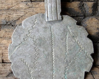 Moroccan tarnished 'coin' disc with scalloped edge and hand engraved design