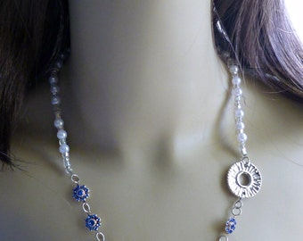 Asymmetrical beaded necklace featuring royal blue Swarovski crystals, silver disc and cream glass pearls