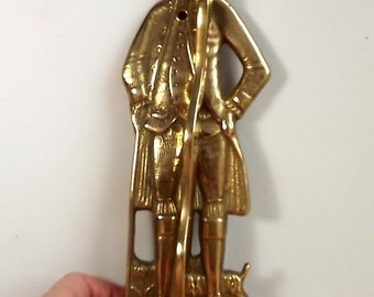 Brass man coat hook in with fold down arm for hanging coats