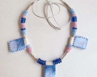 Shibori dyed pendant necklace hand embroidered Native American and African glass beads in pinks, blues and silver on thick silver leather