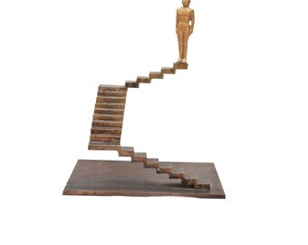 MAN METAL ART. Cast Bronze sculpture. Male figure standing on top of bronze stairs.Signed