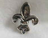 Fleur de Lis pendant in .925 sterling precious metal clay.  It is 1 1/4 inch high and 1 inch across.  Can be work as lariat or on chain.