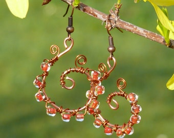 Spiral copper earrings with orange beads