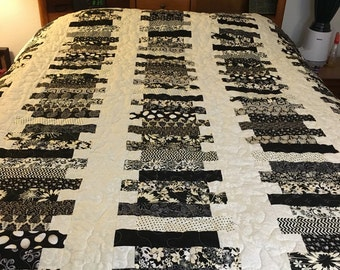This is a new hand sewn queen size quilt featuring black, gray and creams.