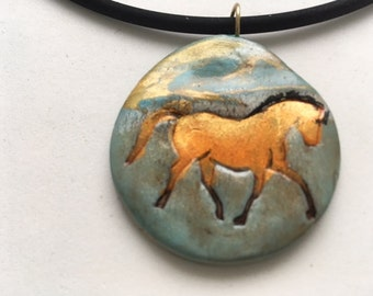 Golden trotting horse polymer clay pendant.