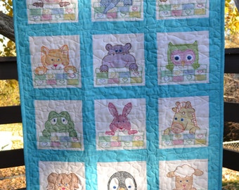 Cross stitched baby quilt featuring animals