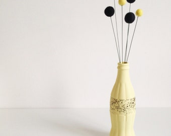 Yellow and black marble effect glass bottle with pom pom flowers